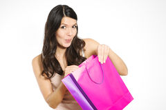 Satisfied female customer with her purchase. Satisfied beautiful young female customer with her purchase held in a purple recyclable paper shopping bag smiling royalty free stock photos