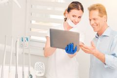 Satisfied female dentist and patient looking at tablet computer. Look at this. Selective focus on a satisfied young dental professional standing next to her male Royalty Free Stock Image