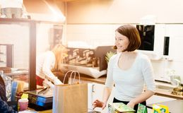 Satisfied female owner of a local store stands smiling behind the counter. Of her small business Royalty Free Stock Photography