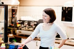 Satisfied female owner of a local store stands smiling behind the counter. Of her small business Royalty Free Stock Photos