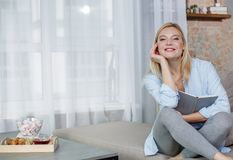 Satisfied female taking rest in living room. Portrait of amused girl sitting on couch and holding book at home. She is looking at camera and laughing. Copy space royalty free stock photos