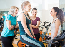 Satisfied females riding stationary bicycles. In modern gym for women Stock Photos