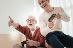 Satisfied friendly natives playing together and having fun. Play together. Satisfied friendly pleasant natives spending time in the bright room playing together Royalty Free Stock Image
