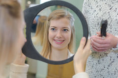 Satisfied girl customer looking at herself on mirror. Satisfied girl customer looking at herself on the mirror stock photography