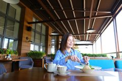 Satisfied girl eating dessert at restaurant  . Gladden female customer eating dessert at restaurant   with satisfied smile. Charming girl enjoying having lunch Royalty Free Stock Photo