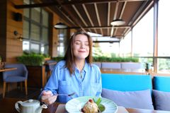 Satisfied girl eating dessert at restaurant . royalty free stock photo