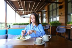 Satisfied girl eating dessert at restaurant  . Gladden female customer eating dessert at restaurant   with satisfied smile. Charming girl enjoying having lunch Stock Photography