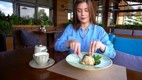 Satisfied girl eating dessert at restaurant. Gladden female customer eating dessert at restaurant in with satisfied smile. Charming girl enjoying having lunch Stock Photos