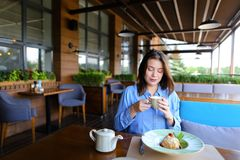 Satisfied girl eating dessert at restaurant  . Gladden female customer eating dessert at restaurant   with satisfied smile. Charming girl enjoying having lunch Royalty Free Stock Image