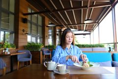 Satisfied girl eating dessert at restaurant  . Gladden female customer eating dessert at restaurant   with satisfied smile. Charming girl enjoying having lunch Royalty Free Stock Images