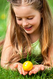 Satisfied girl  is searching easter egg on green grass outdoor. Stock Photos
