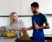 Satisfied girl thanking black professional plumber Royalty Free Stock Photography