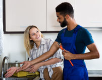 Satisfied girl thanking black professional plumber Stock Photos