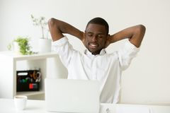 Satisfied happy african american man relaxing with coffee and la. Satisfied happy attractive african american man relaxing hands behind head with coffee and royalty free stock image