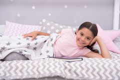 Satisfied with happy end. Girl child lay bed read book. Kid prepare to go to bed. Pleasant time in cozy bedroom. Girl Stock Image