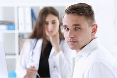 Satisfied happy handsome smiling male patient. With doctor at her office. High level and quality medical service therapeutist consultation work and career Stock Photo