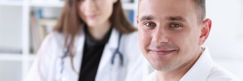 Satisfied happy handsome smiling male patient. With doctor at her office. High level and quality medical service therapeutist consultation work and career Royalty Free Stock Image