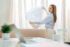 Inspired woman holding a drawing and looking at her table. Satisfied. Happy smiling blond young businesswoman standing at the window and holding a big drawing Royalty Free Stock Image