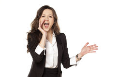Happy woman shouting. Satisfied and happy woman shouting with one hand next to her mouth Royalty Free Stock Photos