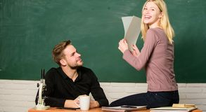 Satisfied with her marks. Couple studying in classroom. Pretty teacher and handsome schoolmaster grading papers. University or college students. Man and women stock photography