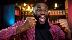 Satisfied with his favourite team victory african-american fan celebrating stock photos