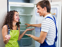 Satisfied housewife grateful to serviceman. For help with fridge Stock Image