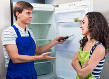 Satisfied housewife grateful to serviceman. For help with fridge royalty free stock images