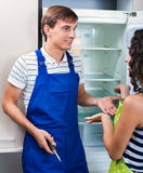 Satisfied housewife grateful to  serviceman. Satisfied housewife grateful to professional serviceman for help with fridge Stock Images