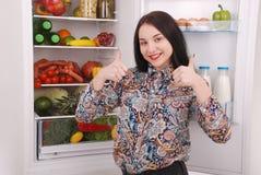 Satisfied housewife near filled fridge. Beautiful young girl near the fridge Stock Image