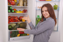 Satisfied housewife near filled fridge. Royalty Free Stock Photos