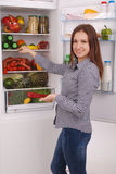 Satisfied housewife near filled fridge. Stock Image