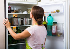 Satisfied housewife near filled fridge Stock Photos