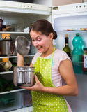 Satisfied housewife near filled fridge Stock Photography