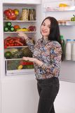 Satisfied housewife near filled fridge. Beautiful young girl near the fridge Royalty Free Stock Image