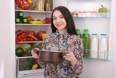Satisfied housewife near filled fridge. Beautiful young girl near the fridge Stock Photo