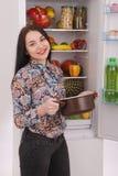 Satisfied housewife near filled fridge. Beautiful young girl near the fridge Royalty Free Stock Photo