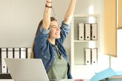 Satisfied intern raising arms at office. Portrait of a young satisfied intern raising arms at office Stock Image