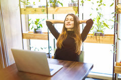 Satisfied with a job done. Happy young businesswoman holding hands behind head and smiling while sitting at her working Royalty Free Stock Photography