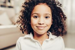 Satisfied kid with wavy locks staring with joy. Portrait of cheerful african child with curly hair looking at camera with delight. Focus on girl Stock Images