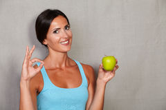 Satisfied lady showing ok sign and toothy smile. While holding apple and looking at camera in fitness tank top against grey texture background Royalty Free Stock Photography