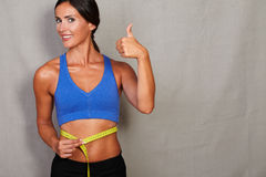 Satisfied lady with thumb up and measuring tape Royalty Free Stock Image
