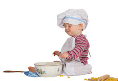 Satisfied little baby chef looking at mixing bowl stock image