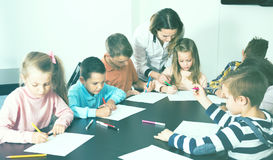Satisfied little children with teacher drawing in classroom. On the lesson Stock Images