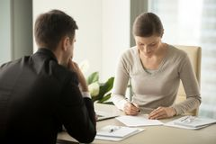Businesswoman signing contract with businessman. Satisfied with loan terms women singing contract when sitting at desk in front of male bank employee at office stock images