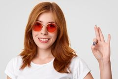 Satisfied lovely Caucasian female in stylish shades, shows okay gesture, aprroves this good idea or plan, smiles pleasantly, shows. White teeth, poses against royalty free stock photo
