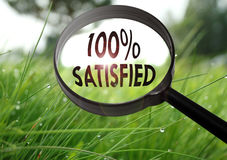 Satisfied. Magnifying glass with the word satisfied on grass background. Selective focus Stock Photos