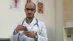 Satisfied male doctor counting money and putting it in his pocket stock video footage