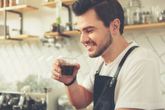 Satisfied male keeping cup in hand and delighting flavor Royalty Free Stock Photography