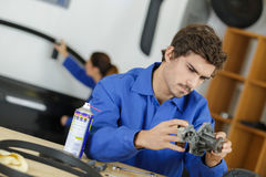 Satisfied male mechanic in auto repair shop Royalty Free Stock Photos