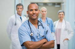 Satisfied male nurse. Confident male nurse in front of his medical team looking at camera. Smiling african young surgeon standing in front of his colleagues with stock image
